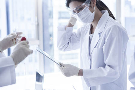 white mask: Serious clinician studying chemical element in laboratory.