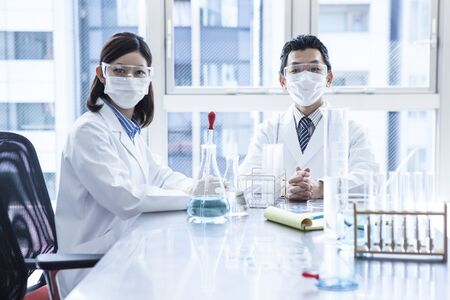 dropper: Two young researchers at work. Stock Photo