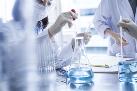 Scientist in laboratory examining liquid in Erlenmeyer flask. Stock Photo