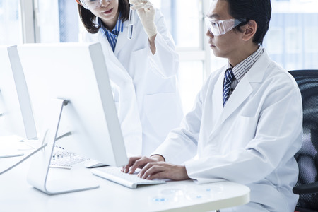 Two scientists and a personal computer and windows. 写真素材