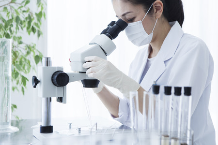 Microscope and female researcher. Stockfoto