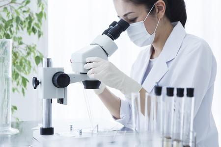 Microscope and female researcher. Foto de archivo