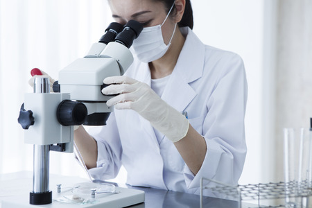 Microscope and female researcher. Stock Photo