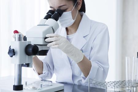 Microscope and female researcher. Archivio Fotografico