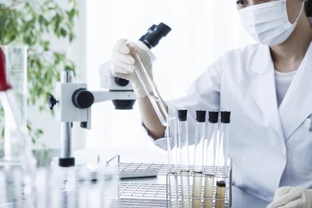experimento: investigador científico mirando un tubo de ensayo en un laboratorio.