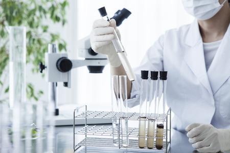 Naukowiec spojrzenie na probówki w laboratorium. Zdjęcie Seryjne