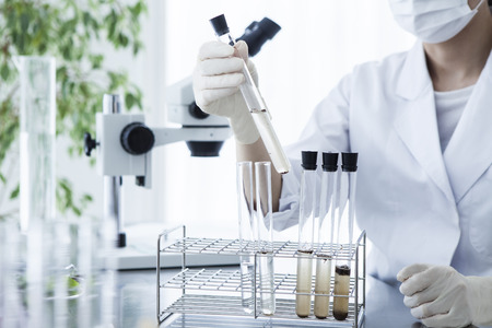 scientific researcher looking at a test tube in a laboratory. Archivio Fotografico