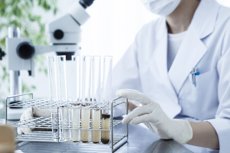 Scientists examine the liquid of a test tube.