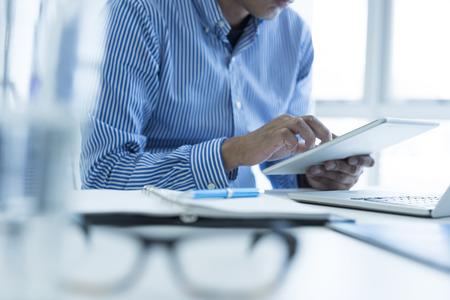 Businessman is using smart tablet.