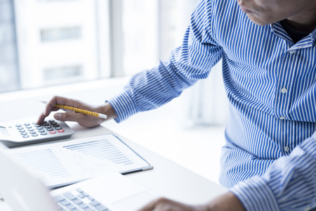 Businessman use the calculator.