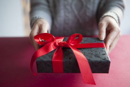 red handed: A woman giving a gift to a favorite person Stock Photo