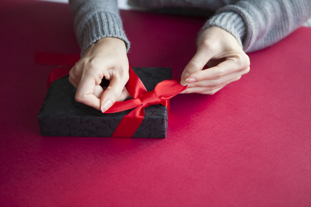 handed: A woman wrapping a gift box