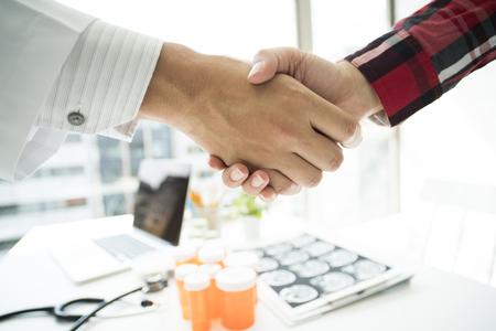クローズ アップは、医師と患者が握手を交わしています。