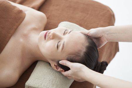 A therapist who massages womens scalp with an esthetic salon.