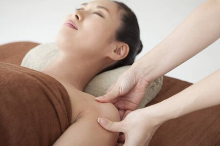 A therapist who is massaging a womans shoulder with an esthetic salon. Stock Photo