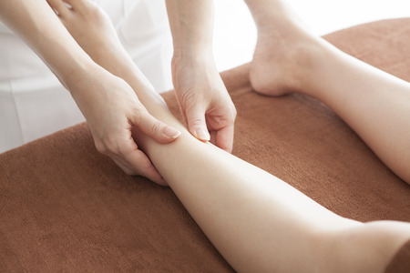 Detail of hands massaging human calf muscle. Therapist applying pressure on female leg.