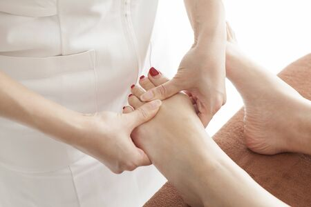 Close-up of female hands doing foot massage.