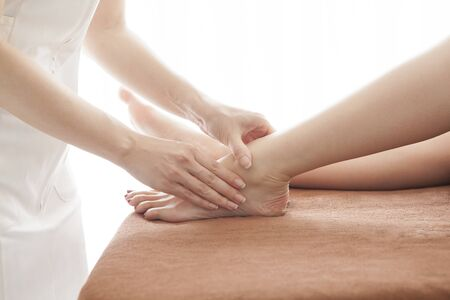 A womans foot and a hand of a woman who massages the foot.