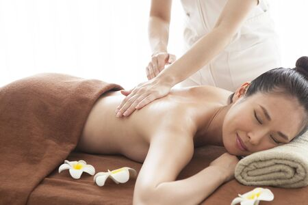 A therapist who is massaging a womans back. Stock Photo