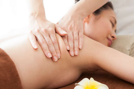 Close up of Therapist doing curative healing massage with thumbs on female back. Stock Photo