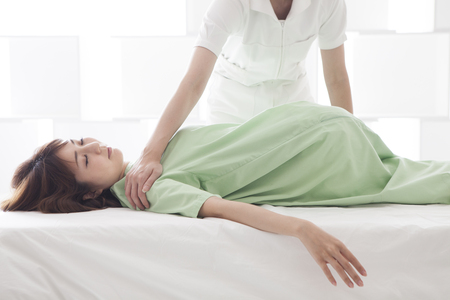 A lady lying on bed, receiving a massage.