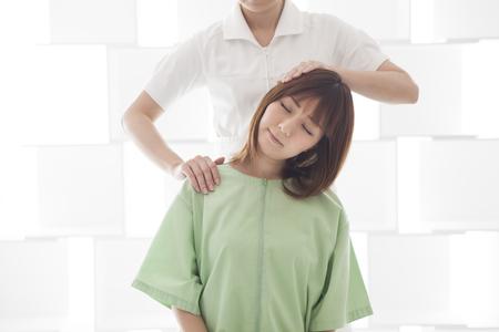 Een vrouw in bed zitten en schouder- en nekmassage ontvangen.