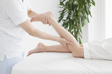 A woman from a chiropractor is massaging a ladys foot.