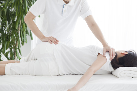 A woman lying on the bed and receiving rehabilitation. Stockfoto