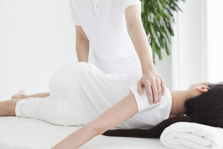 A woman lying on the bed and receiving rehabilitation. Stock Photo