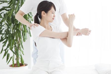 침대에 앉아 어깨와 목 마사지를받는 여자.