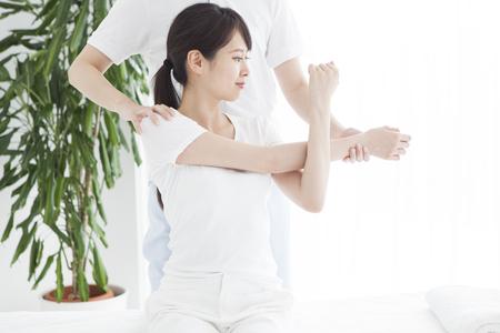 Una mujer sentada en la cama y recibiendo masaje de hombros y cuello.