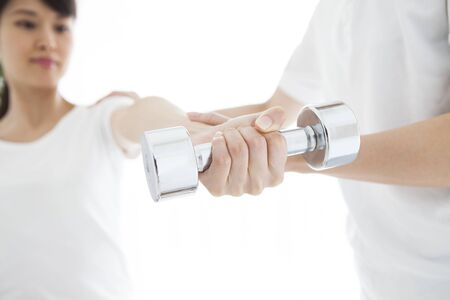 A woman who is rehabilitating with a dumbbell. Stock Photo