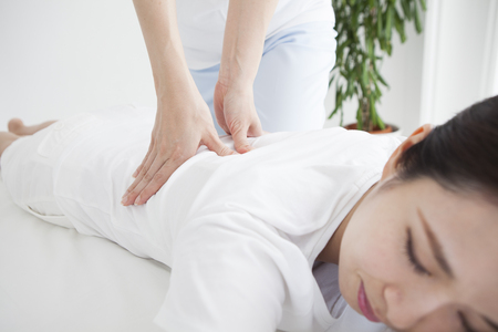 A woman who is shiatsu from a female chiropractor. Stock Photo