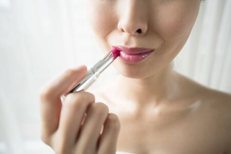 Portrait of a young girl on a white background that paints her lips with pink lipstick.