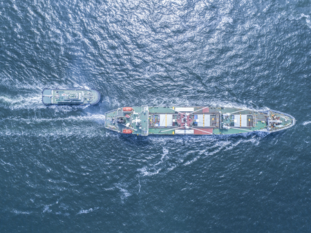 An aerial photograph of a large ship towing a small ship.
