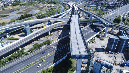 An aerial photograph of a highway under construction. Aerial shooting from diagonally above.
