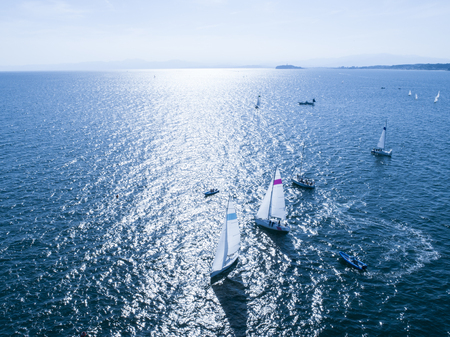 Sea that reflects yachts and sunshine. Shadow of sails. Stock Photo