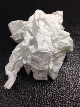 artistic: Crumpled tissue on black background