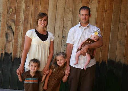 trois enfants: Une jolie jeune famille biparentale avec trois enfants. Banque d'images