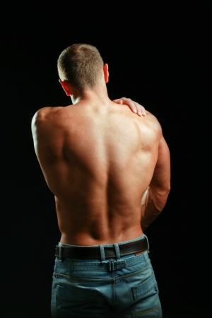 Muscular man with back neck ache isolated on black background photo