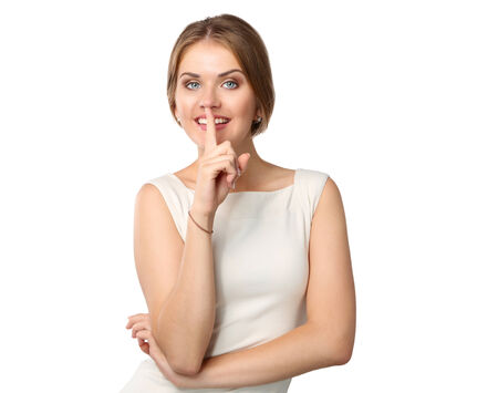 Young woman with finger near lips, standing isolated on white background photo