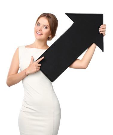 黒い矢印は、白い背景の上に保持している美しい若いビジネス女性 写真素材