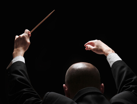 Concert conductor with a baton photo