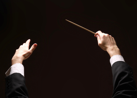 Concert conductor's hands with a baton isolated on a black background Stock Photo