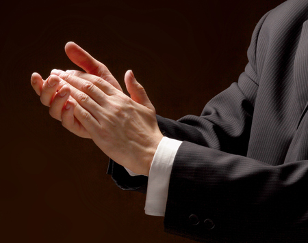approbation: Male hands clapping on black, side-view Stock Photo