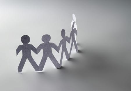 paz mundial: La gente de papel blanco de pie en un círculo y un hombre de papel de color naranja en el interior. Aislado en el fondo blanco