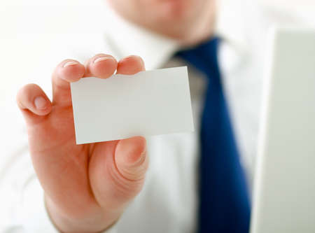 Portrait of young handsome business man holding blank white business card. photo