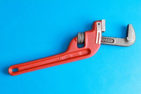 Closeup of adjustable wrench over blue.