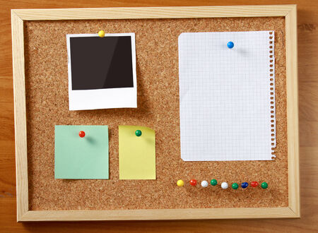 cork board: Cork message board with various paper notes.