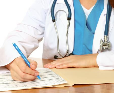 白い背景に分離されてデスクで若い女性医師 写真素材
